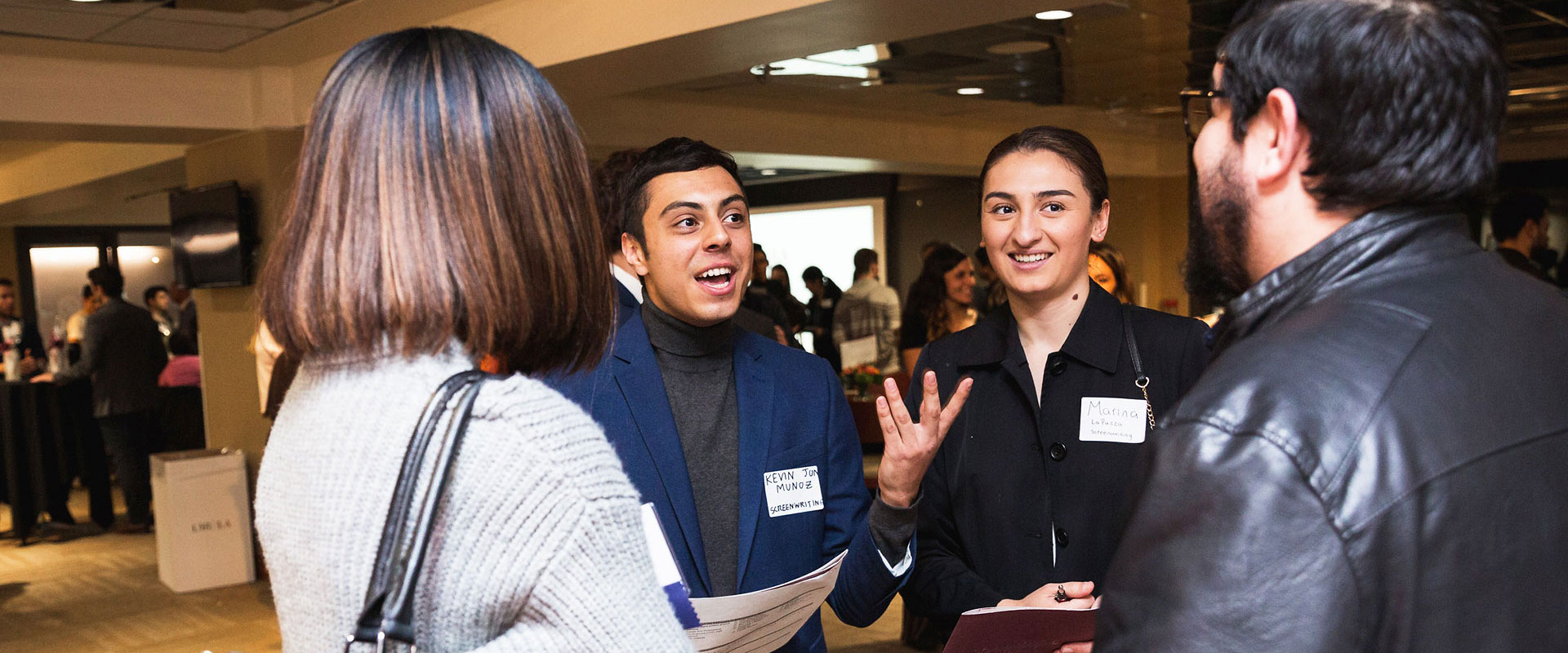 Several students talking to one another at a premier event